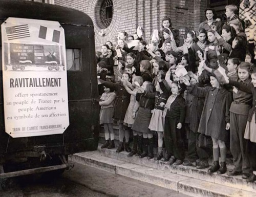 French orphans cheer the arrival of food donations.