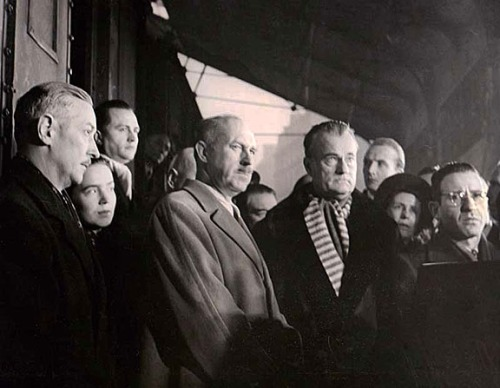In Paris, Drew Pearson (light coat) and other dignitaries await the arrival of relief supplies.