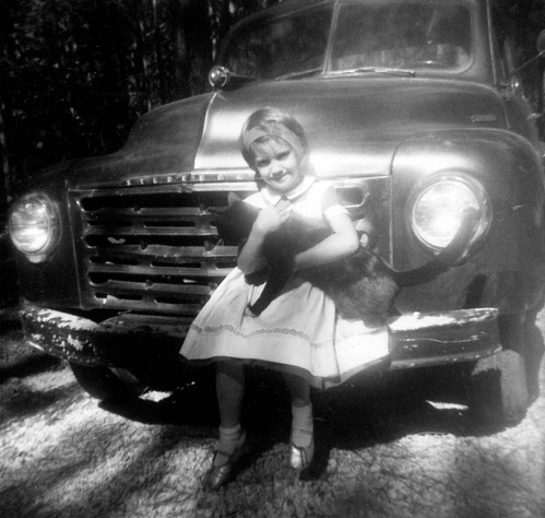 Betty and a struggling cat pose with Old Shakey.
