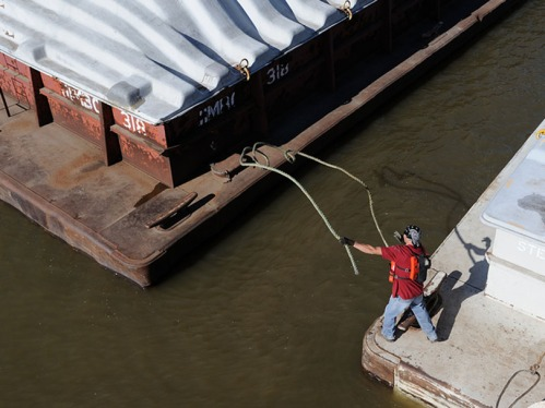 A deckhand casts a line to secure a barge. The same task is performed despite high winds, snowstorms, and icy decks.