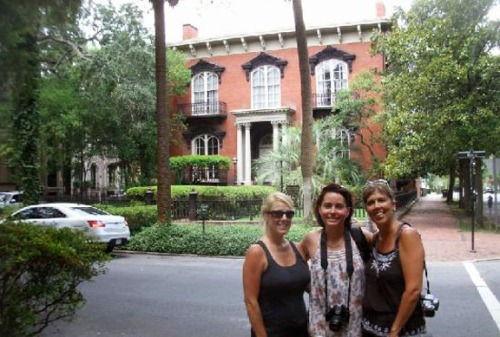 Tourists pose in front of the Mercer House, the scene of the infamous murder.