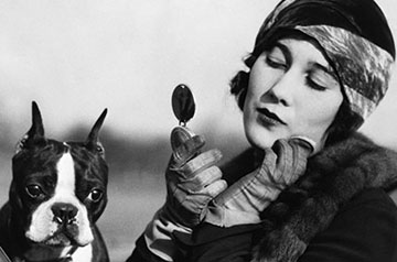 1920s FLAPPER IN CONVERTIBLE POWDERING HER CHEEK IN MIRROR WITH BOSTON BULLDOG IN HER LAP